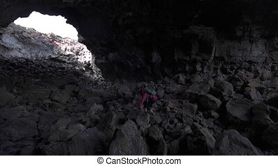 Hiker exploring Indian Tunnel Cave - Young Woman exploring...