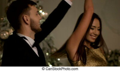 Beautiful young lady and her handsome boyfriend dancing on New Year party.