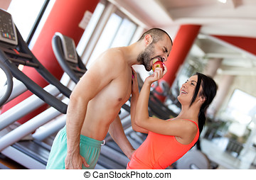 Happy couple in gym feeding each other with apple.