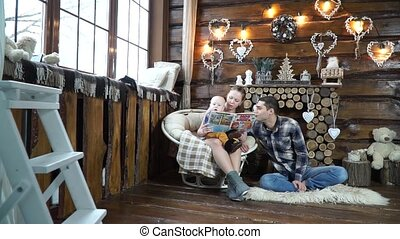 Family reading a story to his son sitting near fireplace -...