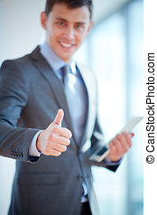 Good job in office - Young businessman giving you thumbs up,...