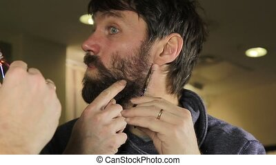 close-up Young Handsome man trimming beard with scissors....