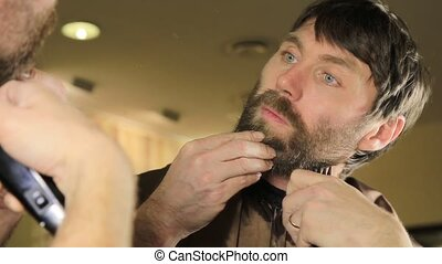 Young Handsome man in beauty saloon working on his beard and...