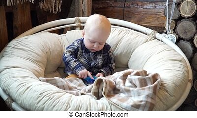 Baby sitting in a chair playing in phone - Baby sitting in a...