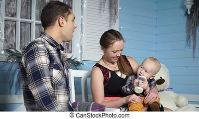 Mom feeds the baby sitting on a bench near his father