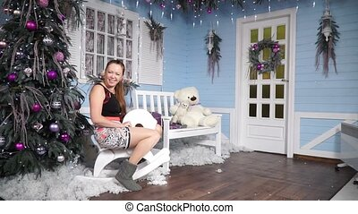 Girl swinging on a rocking horse near a Christmas tree