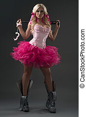 Sexy blonde woman in pink skirt, corset and wristbands