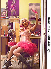Sexy blonde woman in pink skirt and corset doing selfie in...