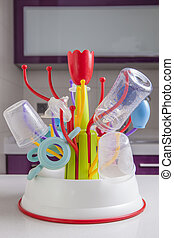 Drainer full of baby plastic tableware objects - Baby...
