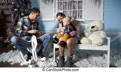 Mom with a child sitting on a bench near his father on a wooden horse