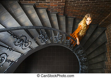 Blond woman in long dress on the stairs