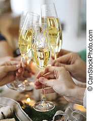 Group of friends toasting with champagne while having...