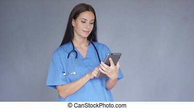 Young female doctor in scrubs using a tablet