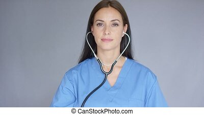 Attractive doctor holding up a stethoscope