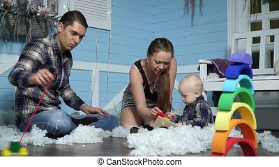 Dad plays with wooden machine while mom and son collect pyramid