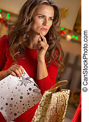 Thoughtful young woman with shopping bags in christmas...