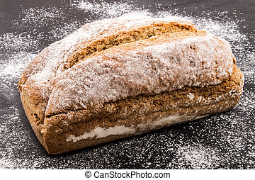 traditional irish soda bread with flour on slate - freshly...