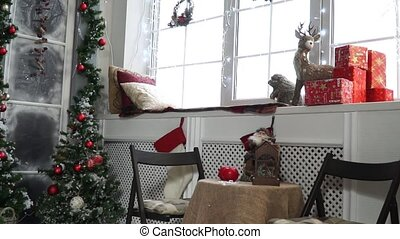 Windowsill with beautiful Christmas decorations and table by...