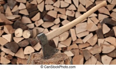 Man chopping firewood with large axe on tree stump - closeup