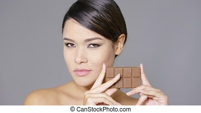 Beautiful smiling woman holding chocolate - Front view close...
