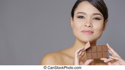Sensual young woman nibbling on a chocolate bar - Sensual...