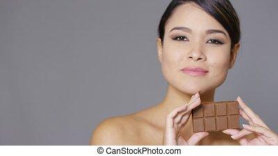 Sensual young woman nibbling on a chocolate bar - Sensual...