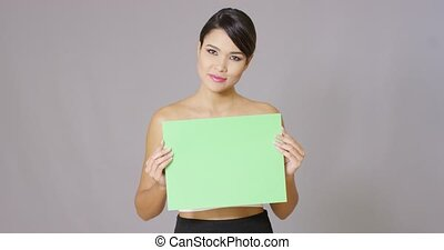 Woman holding a blank card over gray background