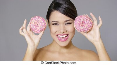 Laughing woman holding two pink donuts to her eyes -...