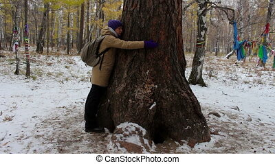 Girl hugging a large old tree in winter forest
