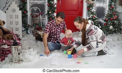 Family with baby draws paint sitting in the snow