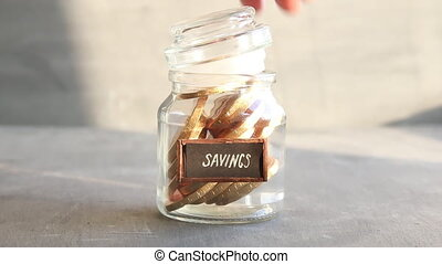 savings concept, money into a glass - Savings idea. Jar with...