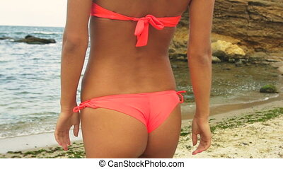 Attractive young blond woman wearing swimming suit, walking...