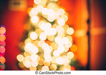 Beautiful  Defocused background new year room with decorated Christmas tree, gifts and fireplace with the glowing lights at night. The idea for postcards. Soft focus. Shallow DOF