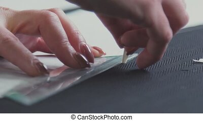 Close-up of a seamstress pursuing a line for drafting...