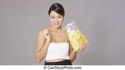 Attractive young woman enjoying a potato crisp opening her...