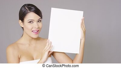 Young woman displaying a blank white sign to the side of her...