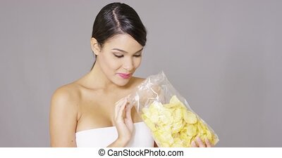 Happy woman grabbing potato crisps - Happy woman grabbing...