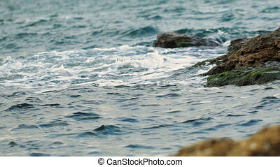 Close up beautiful stony beach in summer time.Waves on a...