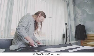 Young woman in a little design studio cutting fabric using a...
