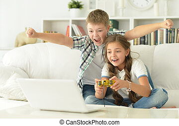 Brother and sister play videogames on laptop sitting at home...