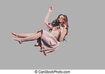 Hovering in air. Studio shot of attractive young woman...