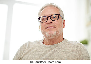 close up of smiling senior man in glasses - old age, vision...