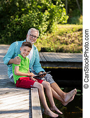 grandfather and boy with tablet pc on river berth - family,...