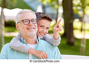grandfather and boy pointing finger at summer park - family,...