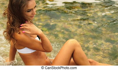 Happy young sexy lady touching her beautiful tanned body,...