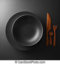 serving of black table with dark wooden utensils and cutlery...