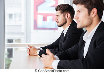 Two concentrated young businessmen sitting in office - Two...