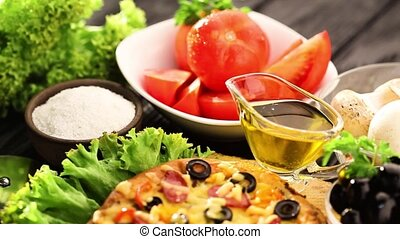pizza and ingredients served on the black wooden table -...