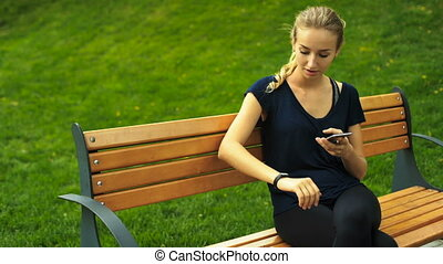 Attractive blond woman sitting on a bench and checking results of her achievements on fitness trackers.