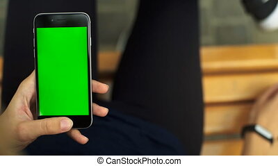 Woman sitting on a bench , checking results on fitness trackers. Green screen Chroma Key. Close up.